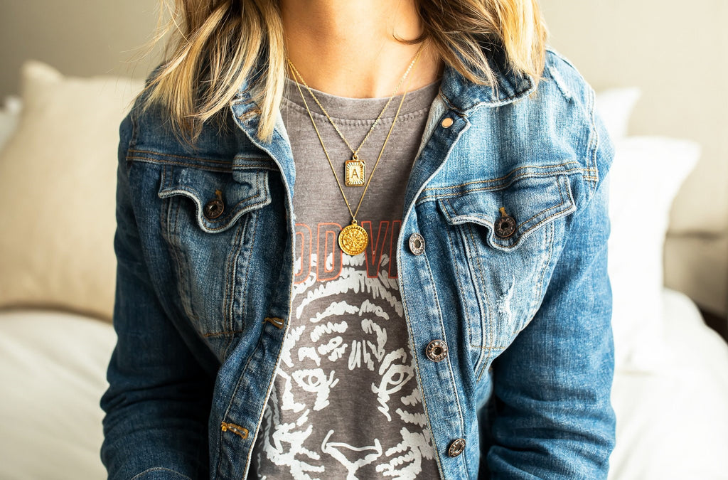 A woman with blonde hair wearing a VICI Collection denim jacket and a lulu and simon graphic tee shirt with two gold layered necklaces made by Meghan Bo Designs.