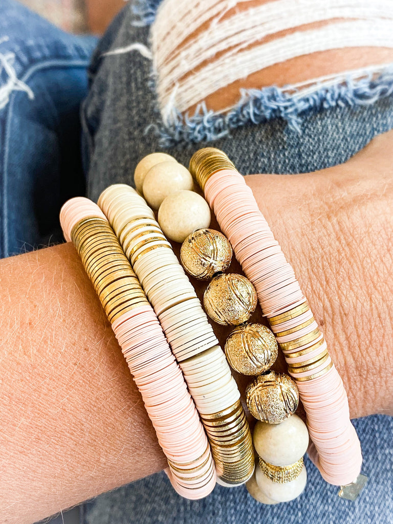 A woman wearing vici collection denim jeans wearing a stack of heishi beaded bracelets.
