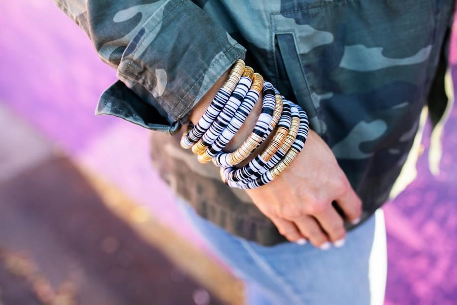 A woman wearing a camouflage jacket and jeans with a stack of black, white and gold heishi beaded bracelets by Meghan Bo Designs.
