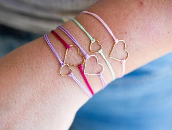 A woman wearing jeans and a tee shirt is lifting her left arm that is wearing a stack of friendship bracelets with gold hearts in purple, pink and  green made by Meghan BO Designs.