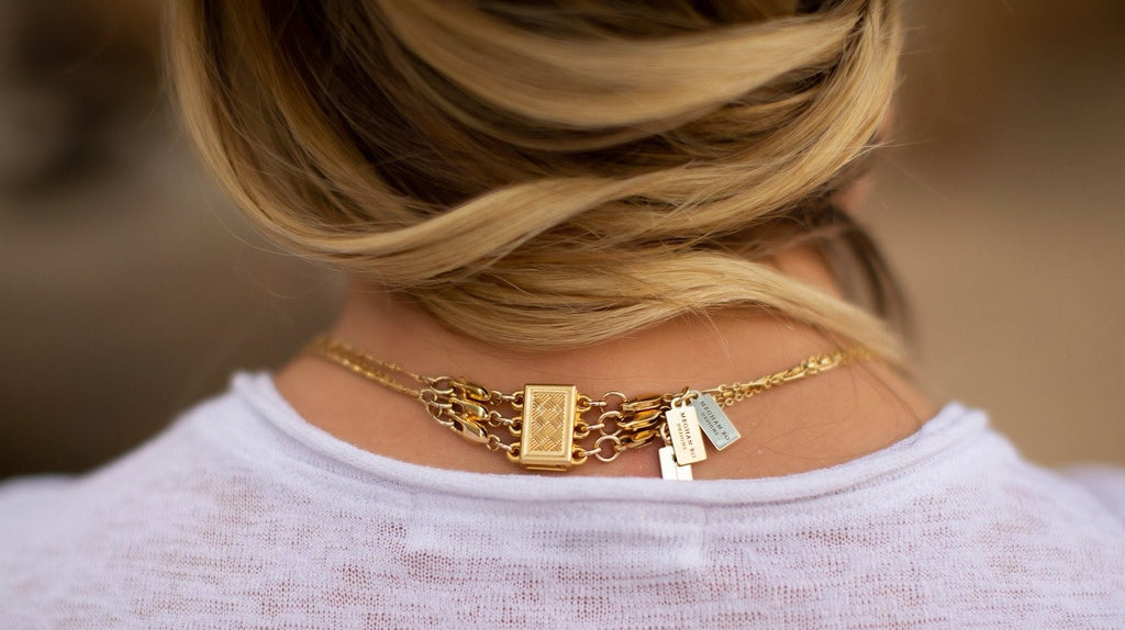 A woman with blonde hair and a white tee shirt has her hair pulled to the side and is wearing three necklaces all attached to one clasp so she doesn't have her necklaces get tangled, made by Meghan Bo Designs.