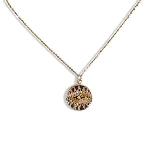 A long gold chain with a coin pendant that has an evil eye on it made by Meghan Bo Designs.