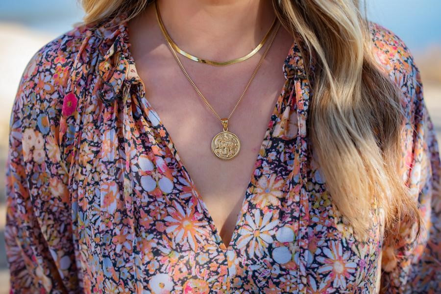 A woman with long blonde hair is wearing a floral Free People dress and two layered gold necklaces, one is a herringbone chain and one is a coin necklace with a dragon on it made by Meghan Bo Designs.
