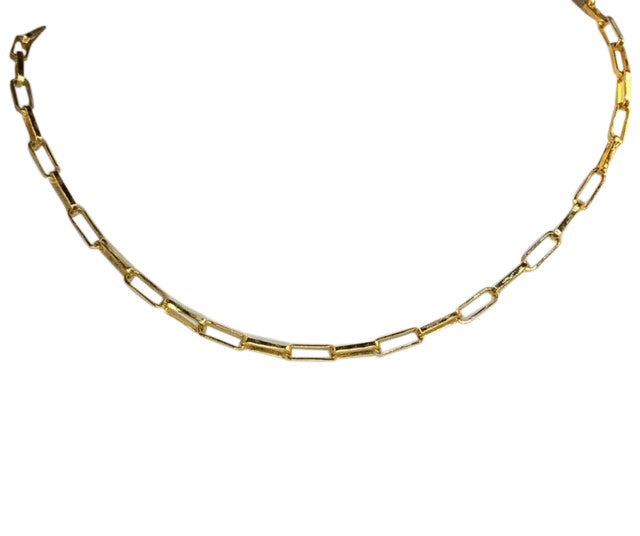 A gold paperclip chain link necklace made by Meghan Bo Designs lays on a flat white surface.
