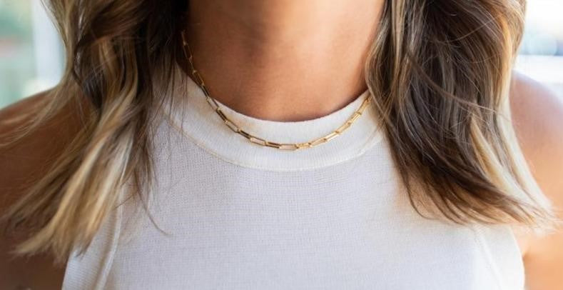 A woman with brown wavy hair is wearing a white vici collection tank top and a choker made with paperclip links made by Meghan Bo Designs.