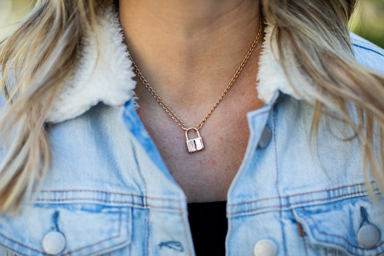 A woman with long wavy blonde hair is wearing a jean jacket and black top with a gold chain link necklace that has a gold lock pendant on it made by Meghan Bo Designs.