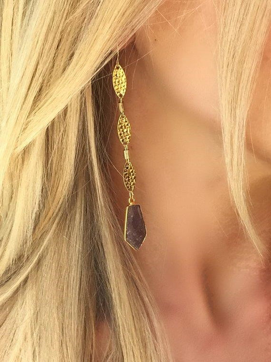 A woman with blonde hair is wearing a gold dangle earring with a lepidolite gemstone at the bottom made my Meghan Bo Designs.