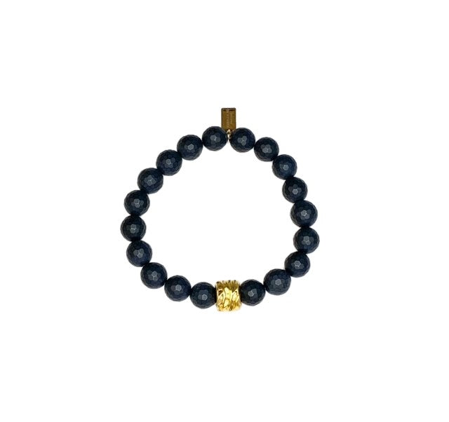 A black beaded bracelet with a gold accent bead made by Meghan Bo Designs lays on a flat white surface.