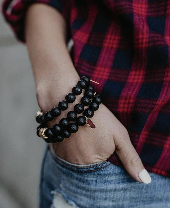 A woman wearing a red plaid shirt and jeans has her right hand in her pocket and is wearing a stack of bracelets with black beads and one gold bead made by Meghan Bo Designs.