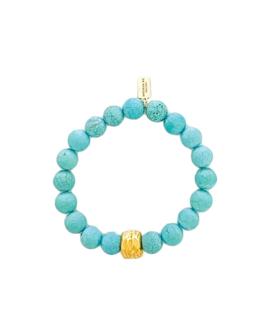A matte turquoise beaded bracelet with a gold accent bead lays on a white surface made by Meghan Bo Designs.