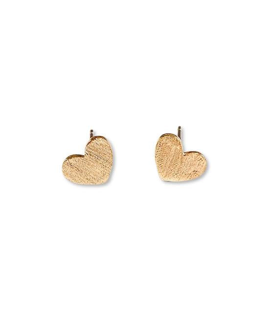 A small pair of brushed gold heart stud earrings lay on a white surface made by Meghan Bo Designs.