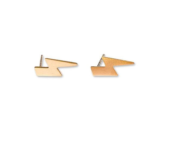 A small pair of gold lightning bolt stud earrings lays on a white surface made by Meghan Bo Designs.