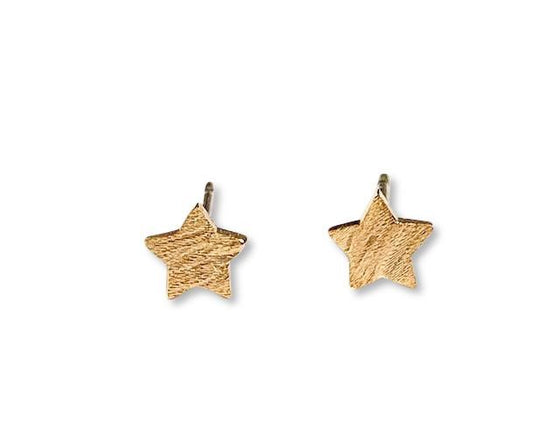 A pair of brushed gold small star stud earrings made by Meghan Bo Designs lays on a white surface.