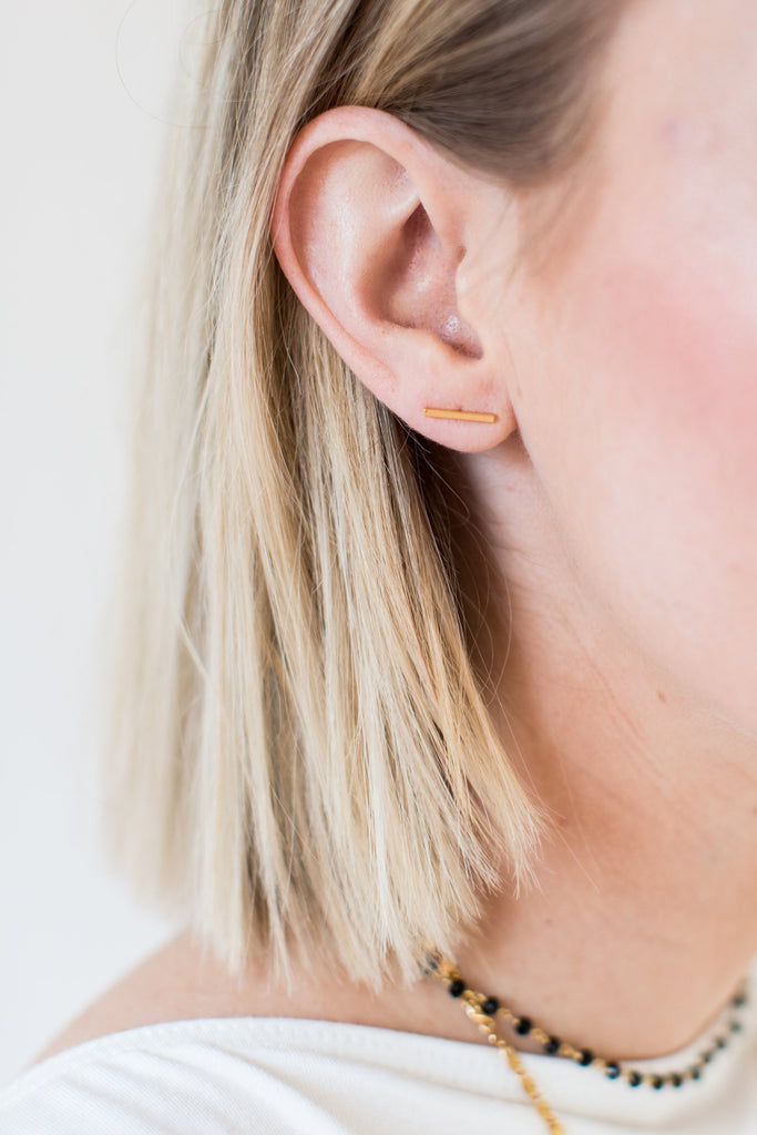 A woman with straight blonde hair wearing a white tee shirt from Vici Collection is turned to the side and is wearing a pair of small gold bar stud earrings by Meghan Bo Designs.