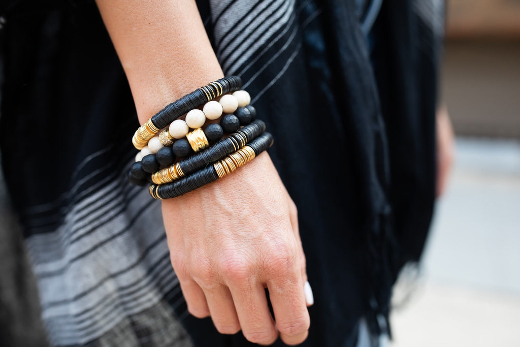 Woman wearing a black outfit and a stack of Black and Gold beaded stretch bracelets from Meghan Bo Designs.