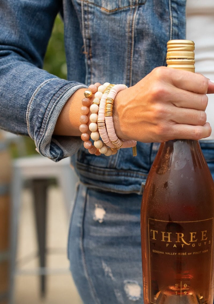 A woman wearing a Vici Collection denim jacket and jeans holding a bottle of rose wine wearing a stack of pink beaded stretch bracelets by Meghan Bo Designs in Sonoma California.