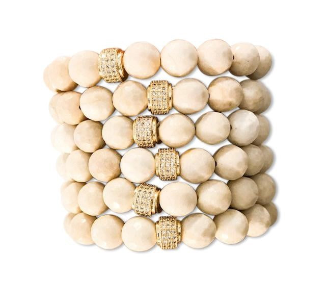 A stack of bracelets that are made with  ivory colored fossil stone beads and a gold accented cubic zirconia beads lay on a white surface made by Meghan Bo Deisgns.
