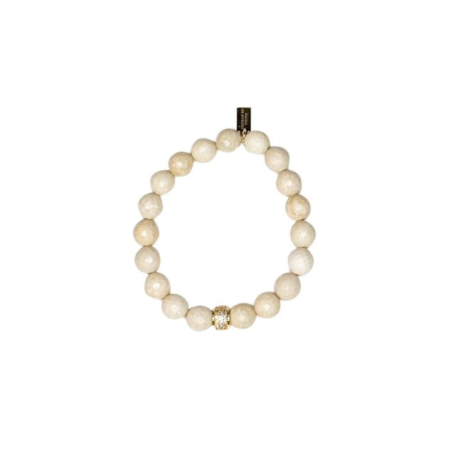 An ivory colored beaded bracelet with a cubic zirconia accent bead made by Meghan Bo Designs lays on a flat white surface.