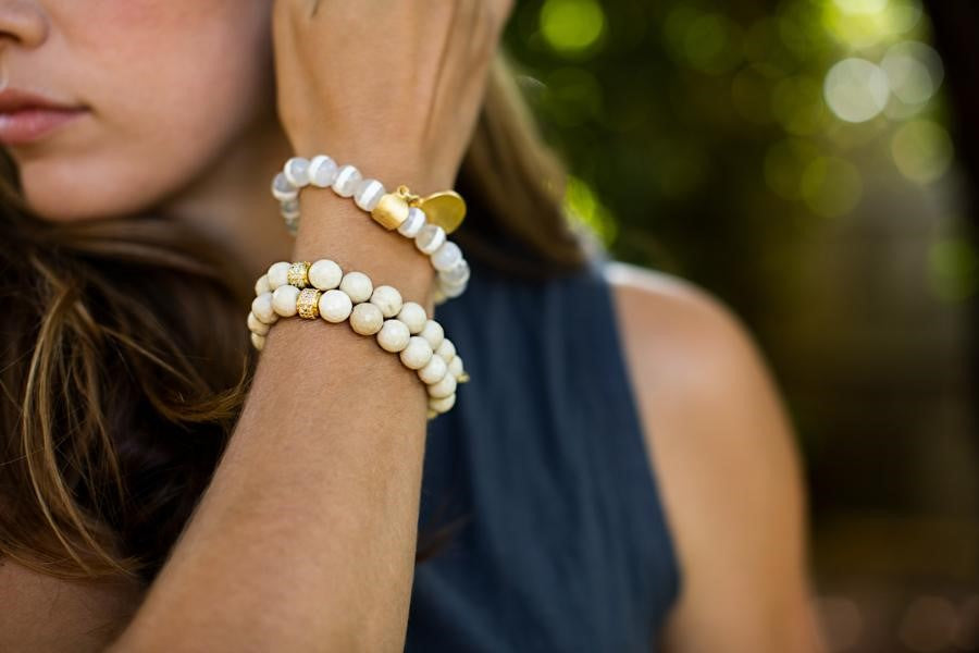 A woman with long brown hair brushes her hair back with her right hand and is wearing a stack of bracelets made with ivory colored fossil stone beads by Meghan Bo Designs.