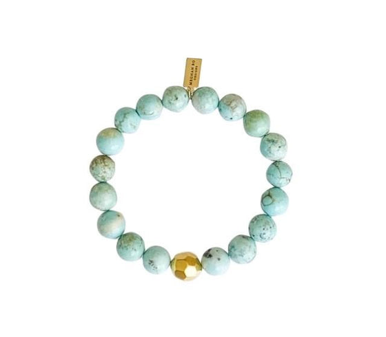 A light green beaded stretch bracelet with gold accents made by Meghan Bo Designs lays on a flat white surface.