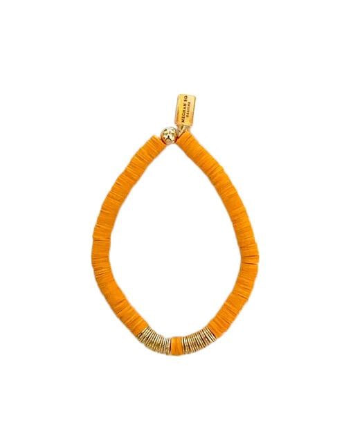 An orange and gold heishi beaded bracelet made by Meghan Bo Designs lays on a white surface.