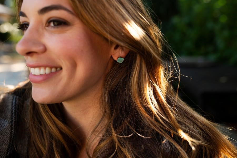 A woman with long brown hair looks to the side smiling, she is wearing a pair of round turquoise stud earrings that have a gold edge on them made by Meghan Bo Designs.