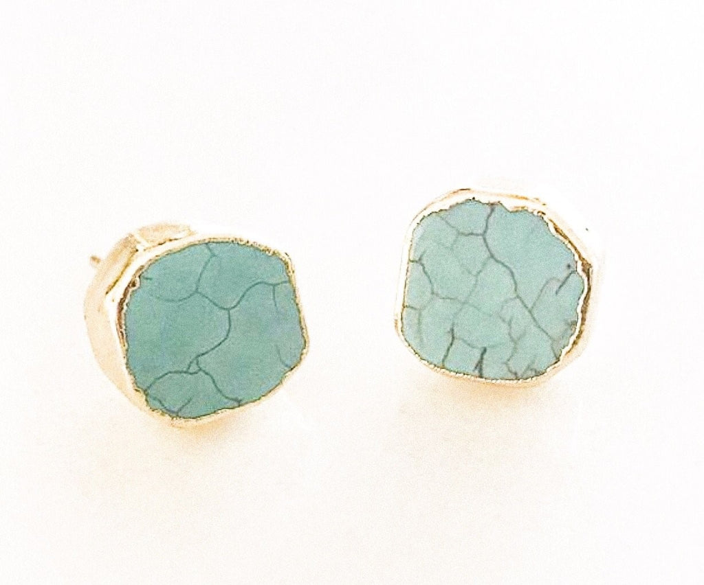 A pair of round turquoise stud earrings that have a gold edge lay on a white background made by Meghan Bo Designs.