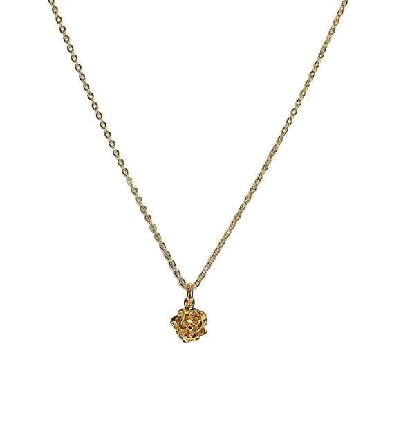 A gold chain necklace with a flower pendant made by Meghan Bo Designs lays on a flat white surface.