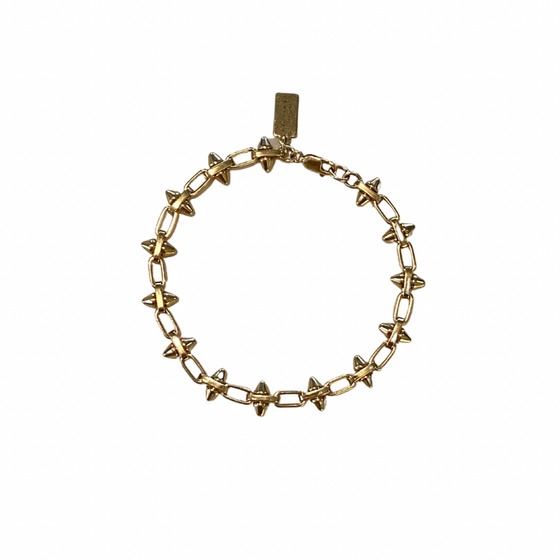 A gold chain bracelet with spikes on it made by Meghan Bo Designs lays on a flat white surface.