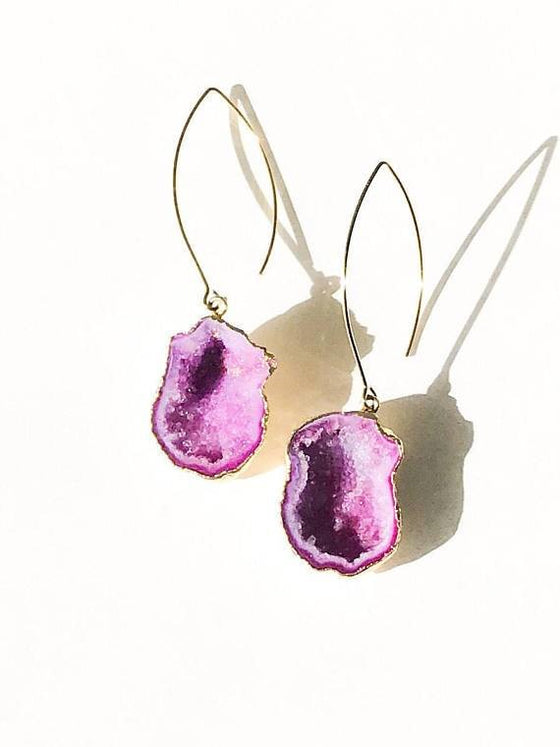A pair of pink geode earrings on a gold ear wire lay on a white surface.