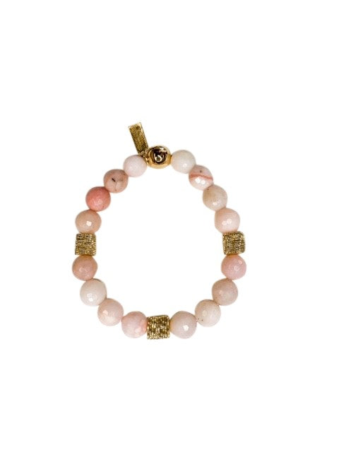 A beaded stretch bracelet with pink opal and gold beads made by Meghan Bo Designs lays on a white surface.