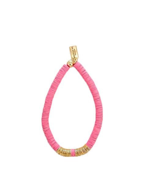 A pink heishi beaded bracelet with gold accents made by Meghan Bo Designs lays on a flat white surface.