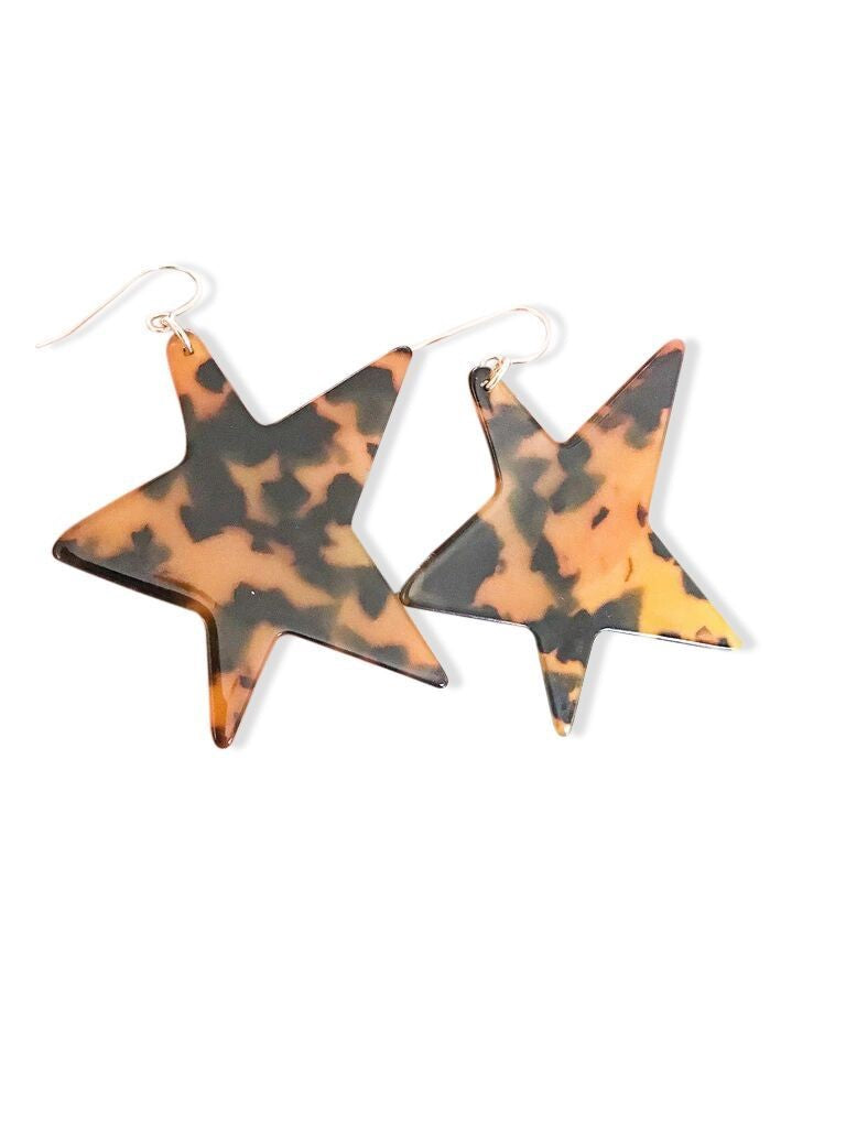 A pair of large tortoise shell star shaped earrings with a gold fill ear wire made by Meghan Bo Designs lay on a flat white surface.