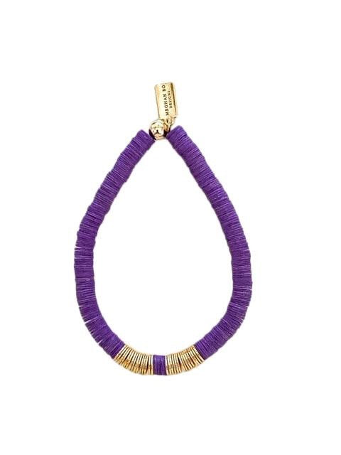 A purple heishi beaded stretch bracelet with gold accents made by Meghan Bo Designs lays on a flat white surface.