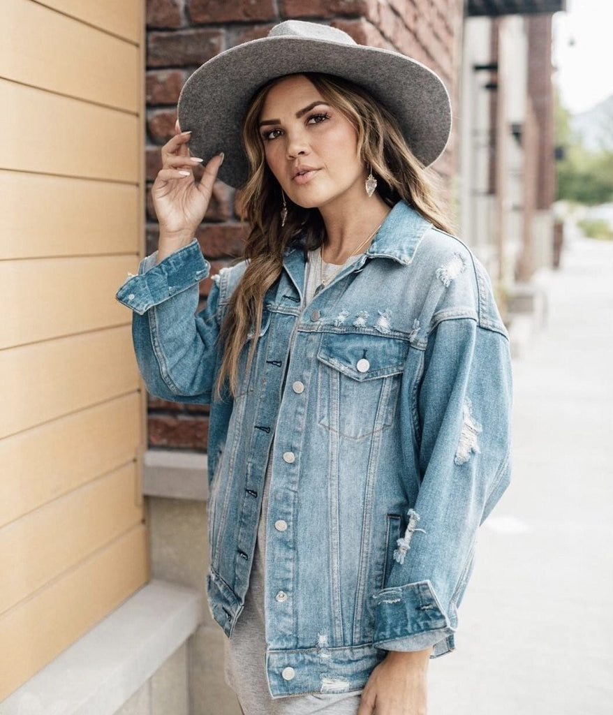 Kristin Rose Davis wearing Meghan Bo Designs quartz arrowhead drop earrings, a denim jacket and a felt grey hat