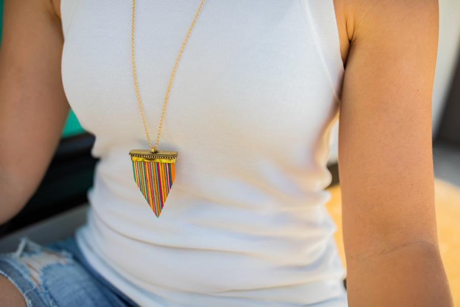 A woman wearing a white sleeveless VICI shirt and jean shorts is wearing a long necklace with a rainbow painted wooden arrow pendant on it made by Meghan Bo Designs.