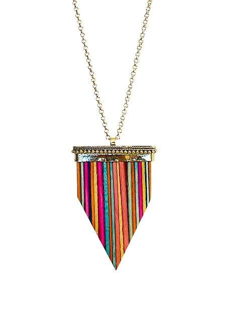 A rainbow painted wooden arrow pendant on a gold fill chain made by Meghan Bo Designs lays on a flat white surface.
