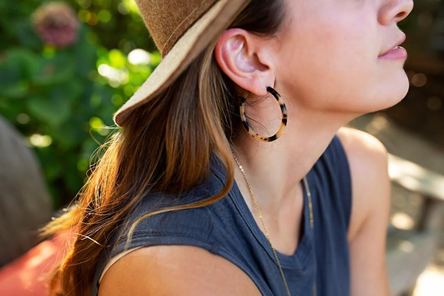 A woman with long brown hair is wearing a sleeveless blue tee shirt and a brown hat looks to the side wearing a pair of tortoise shell hoop earrings made by Meghan Bo Designs.
