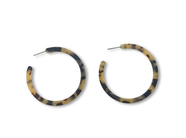 A pair of tortoise shell hoop earrings made by Meghan Bo Designs lay on a flat white surface.