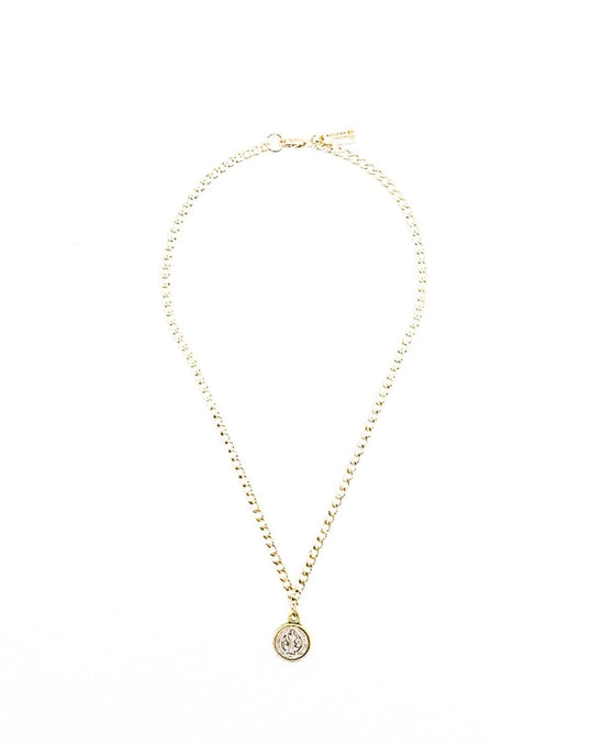A two toned circle pendant that is silver and gold with a saint on it hangs from a gold chain made by Meghan Bo Designs lays on a flat white surface.