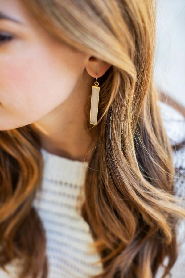 A woman with long brown wavy hair is wearing a white sweater and selenite crystal dangle earrings made by Meghan Bo Designs.
