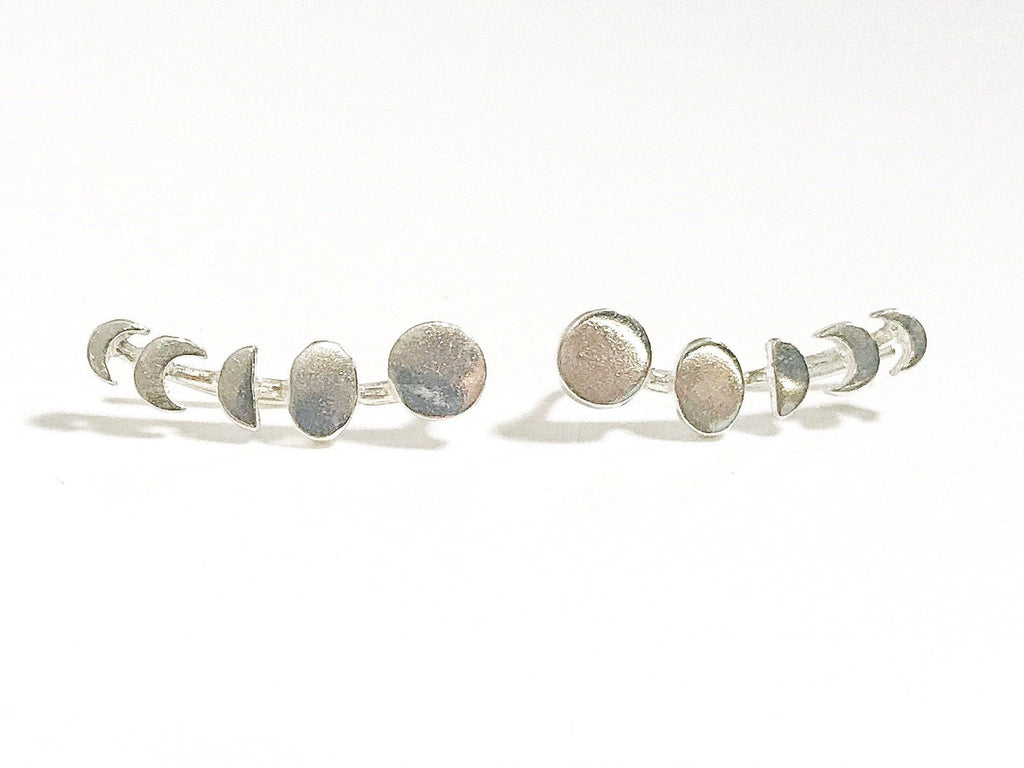 A pair of silver phases of the moon ear climbers made by Meghan Bo Designs lays on a flat white surface.