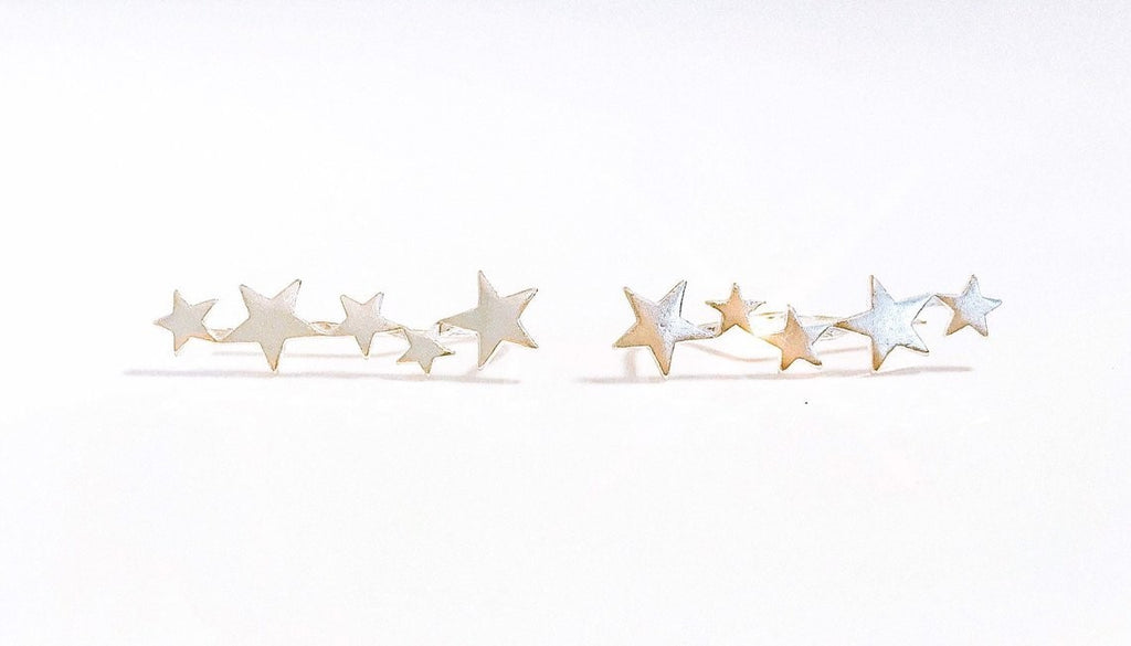 A pair of silver star ear climbers made by Meghan Bo Designs lay on a white surface.