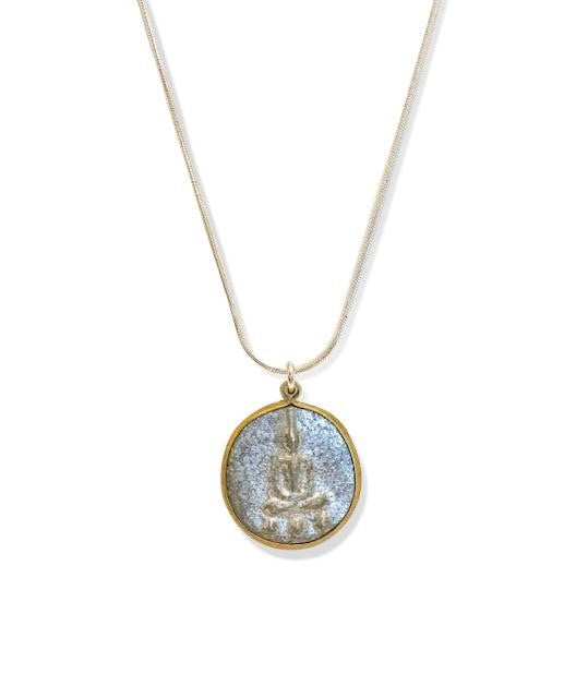 A silver chain necklace with a silver Buddha pendant made by Meghan Bo Designs lays on a white surface.
