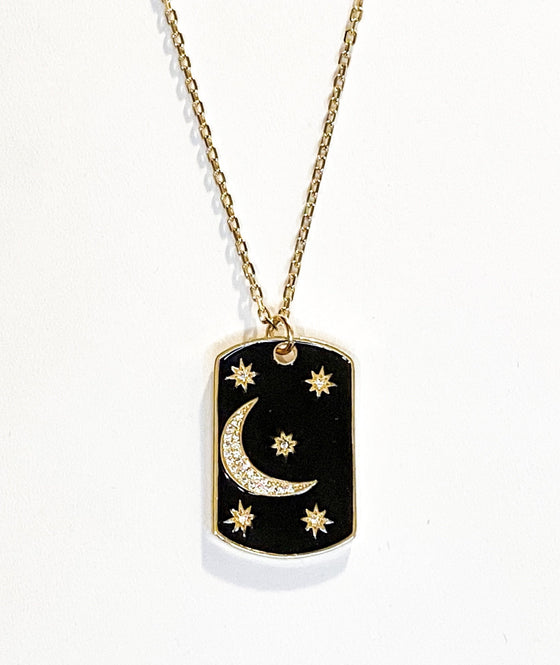 A gold chain with a black enamel rectangle pendant with cubic zirconia stars and a moon made by Meghan Bo Designs lays on a white surface.