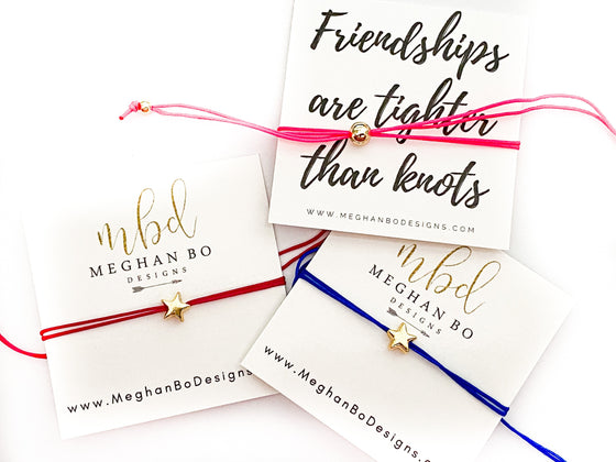 Three friendship bracelets on jewelry cards lay on a flat white surface, each bracelet has a gold star and gold fill accent beads with multiple string colors made by Meghan Bo Designs.