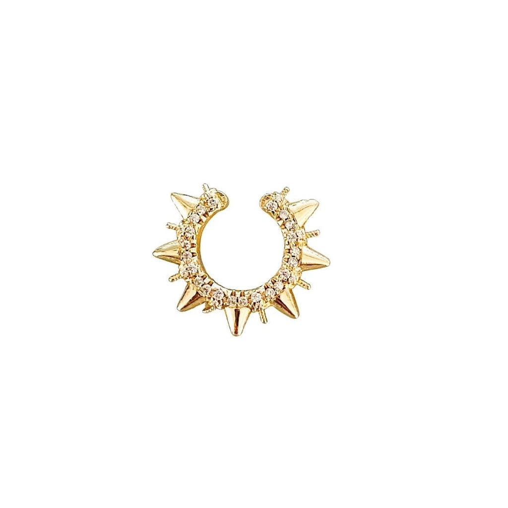 A gold ear cuff earring with cubic zirconia and spikes made by Meghan Bo Designs lays on a flat surface.