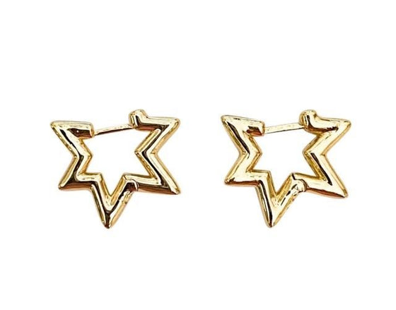 A pair of gold star earrings made by Meghan Bo Designs lay on a flat white surface.
