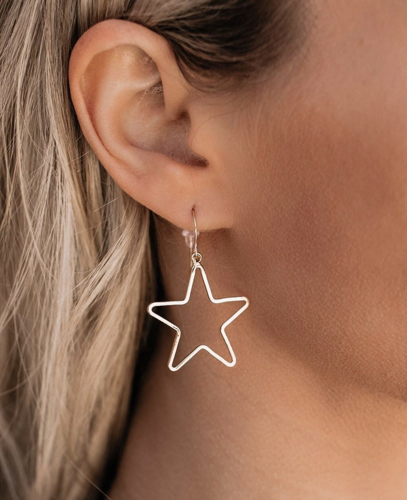 A woman with blonde hair is wearing a gold star earring with a gold ear wire made by Meghan Bo Designs.