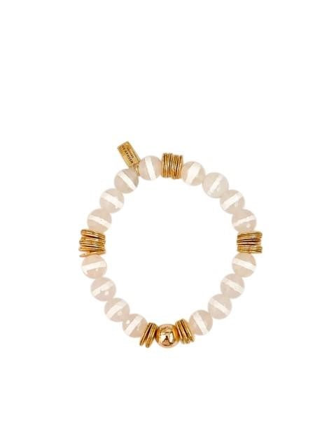 A beaded stretch bracelet with clear beads with a white stripe and gold accent beads made by Meghan Bo Designs lay on a flat white surface.